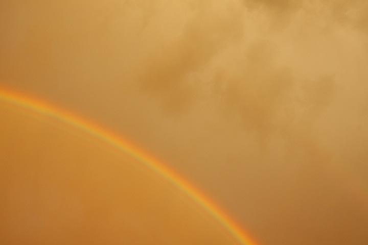 Goldener Himmel mit Regenbogen.